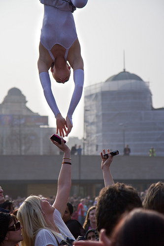 Upside-down performer reaches down to answer a phone call