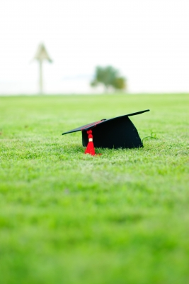 Graduation hat in a grassy field