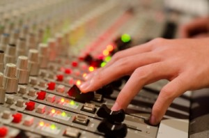 Game sound designer works a mixing board
